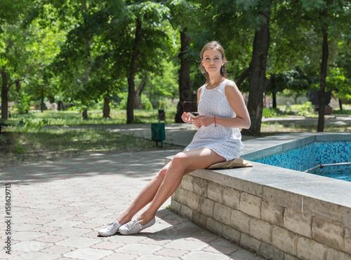 Fotografia, Obraz  Young beautiful girl in short white dress sit near fountain