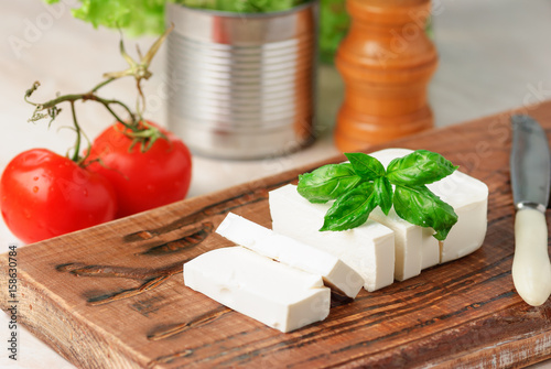Feta cheese decorated with fresh basil leaf on a wooden board. close up and selective focus
