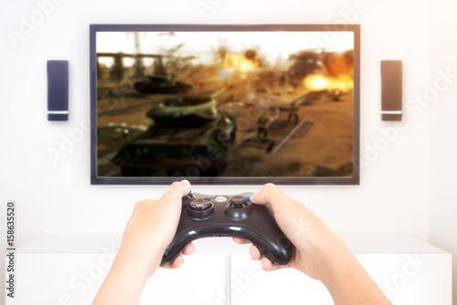 Zdjęcie XXL Gracz grający konsoli wojennej gry wideo trzyma gamepad - wysoki kluczowy wizerunek