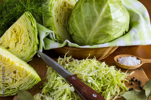 Photographie Cabbage and chopped cabbage on the light brown wooden background