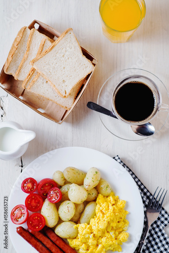Foto op Plexiglas Gebakken Eieren Traditional American breakfast, hotel or restaurant, boiled potato with dill, smoked sausage, omelette from chicken eggs, fresh cherry tomato, white toast, milk and black coffee on a light background