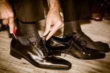 Groom Wearing Shoes On Wedding Day Tying The Laces