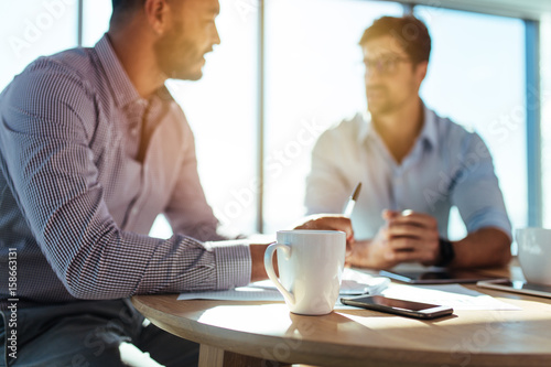 Fotomural  Business investors discussing business matters sitting at table