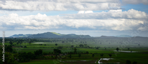 Spoed Foto op Canvas Grijze traf. landscape panorama with view of green field and mountains on rainy day