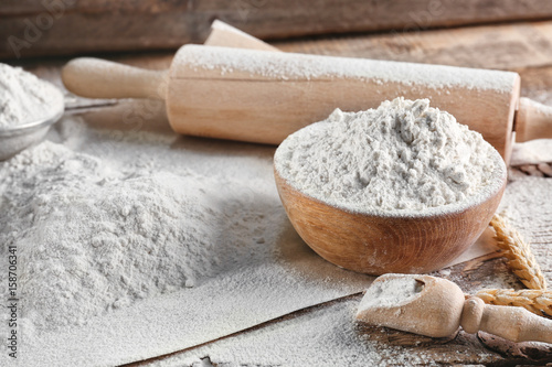 Fényképezés Bowl of flour and rolling pin on wooden background
