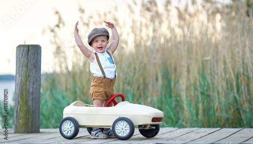 zabawa-nad-jeziorem-niebieskooki-chlopiec-w-samochodziku-na-pomoscie