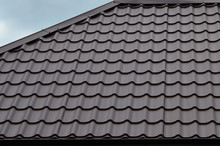 Brown Roof Tiles Or Shingles On House As Background Image. New Overlapping Brown Classic Style Roofing Material Texture Pattern On A Actual House
