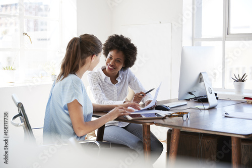Photo  Two young women discussing documents at a desk in an office