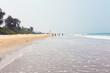 Tropical sandy beach, sunny sky and calm blue ocean on a clear day.
