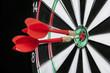 Darts hitting the center target of a dartboard