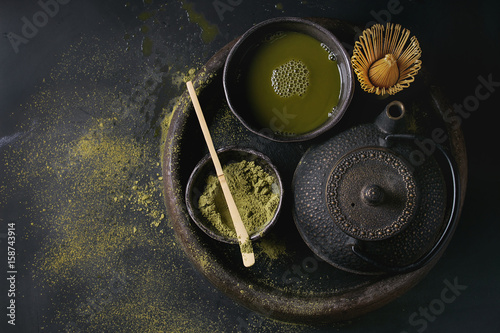 Green tea matcha powder and hot drink in black bowls standing with iron teapot, bamboo traditional tools spoon and whisk in terracotta tray over dark metal background Canvas Print