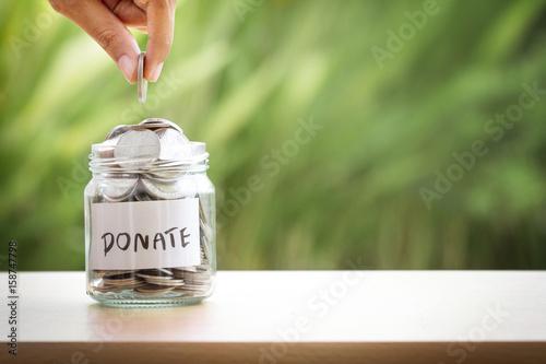 Hand putting Coins in glass jar for giving and donation concept Tapéta, Fotótapéta