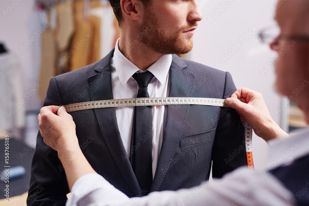 Fototapeta Mid section portrait of tailor fitting bespoke suit to model