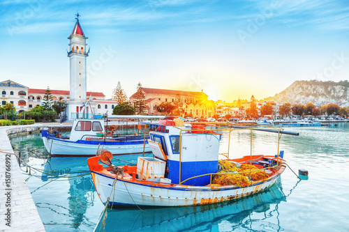 Zante - Zakinthos island, old port with moored boats and church tower landmark. Majestic sunset scenery, sun glowing visible.