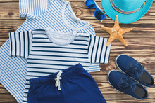 Flat Still Of Child Wear. Kid`s Wardrobe. Beach And Vacation Clothes For A Little Boy.Wooden Background