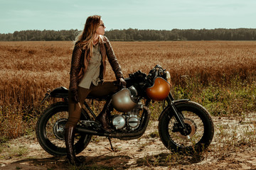Fototapeta na wymiar Woman rider with his vintage custom made cafe racer
