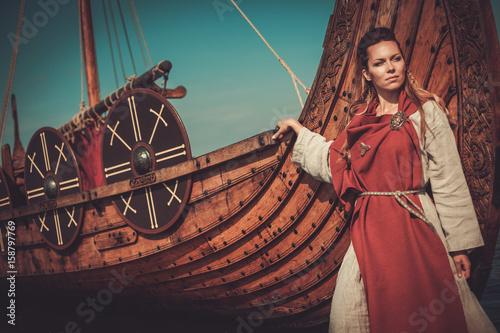 Plakát  Viking woman in traditional clothes near drakkar