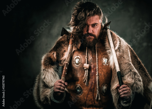 Photo  Viking with cold weapon in a traditional warrior clothes
