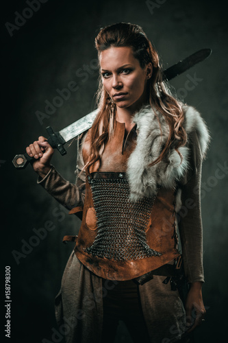 Fotografía  Viking woman with cold weapon in a traditional warrior clothes