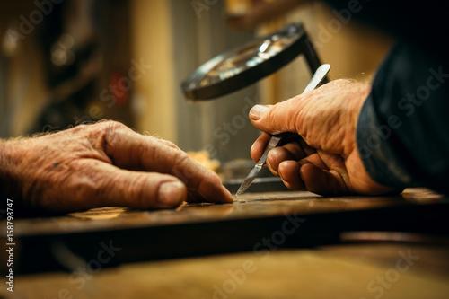 Valokuva  Senior wood carving professional during work