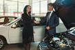Car dealer employee in a jacket shakes a girl's hand to a buyer after a successful transaction. Near the car with an open hood.