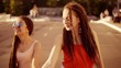 Two happy women with dreads walking on the empty road and talking in summer. Two hipster girls laughing and dancing during a bright sunny day. Slowmotion shot.
