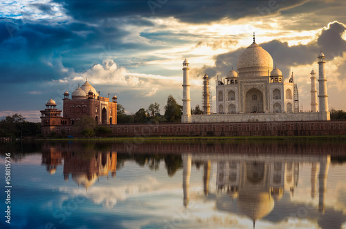 Poster Artistic monument Taj Mahal with a moody sunset sky on the banks of river Yamuna. Taj Mahal is a white marble mausoleum designated as a UNESCO World heritage site at Agra, India.