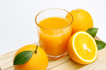 Glass of fresh orange juice with group of orange on a wooden box isolate on white background, Selective focus on glass.