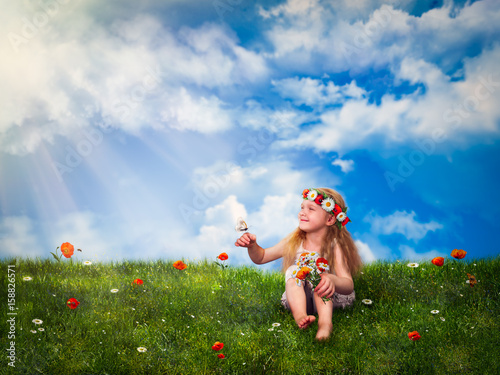 Little girl sitting on green grass and squinting in the sun Canvas Print