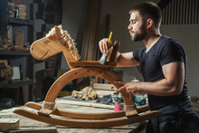 A Young Man Paints A Wooden Toy With A Paint Brush With A Protective Varnish, Made By Himself From The Tree In The Workshop