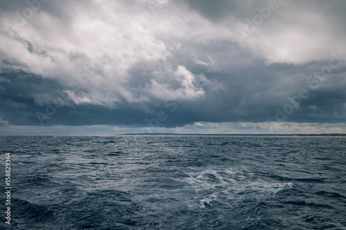 Staande foto Zee / Oceaan Gloomy weather at sea with rain clouds