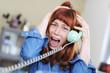Frau mit roten Haaren und Pony schreit in ein Telefon und ist dabei emotional
