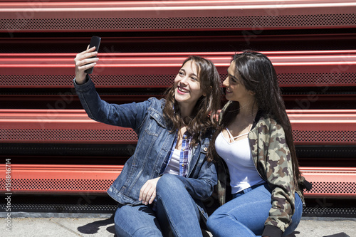 Young women sitting on ground and posing for selfie in sunny day together.