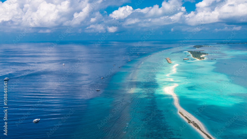 Fototapeta Maldives beach from birds eye view. Aerial view on Maldives island, Ari atoll. Tropical islands and atolls in Maldives from aerial view. Summer holiday beach landscape background in Maldives.