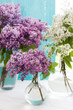 Three bouquets of lilac in round transparent vases near window