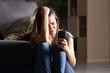 Sad teen checking phone at home