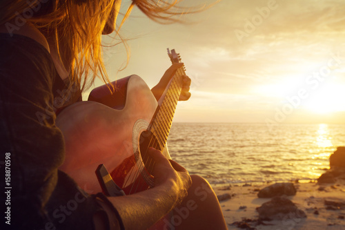 Beautiful young woman playing guitar on sunset beach Fototapet