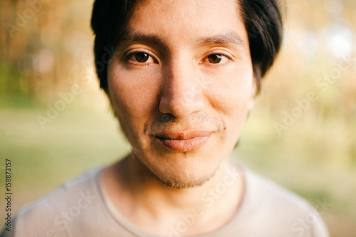 Fototapeta Close up portrait of native american peruvian indian man with black hair, dark eyes looking at camera with deep reflective and stare eyes