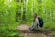 Tourist girl with backpack is sitting on the tree bark in the green forest