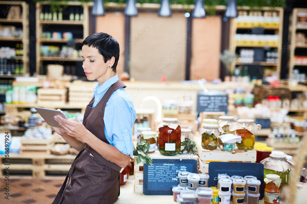 Fototapeta Profile view of confident shop assistant checking quantity of product units in warehouse with help of digital tablet,  lovely store of organic products on background