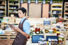 Profile View Of Confident Shop Assistant Checking Quantity Of Product Units In Warehouse With Help Of Digital Tablet,  Lovely Store Of Organic Products On Background