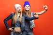 canvas print picture - Two teenage girls friends in hipster outfit make selfie on a pho