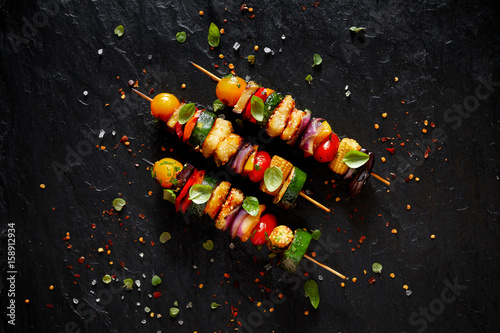 Foto auf Leinwand Grill / Barbecue Vegetarian skewers with halloumi cheese and mixed vegetables on black background, top view