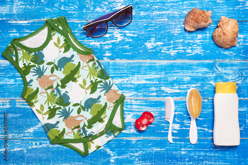Papiers peints Retro Baby Child summer stuff to the beach on a blue wooden background. Top view with copy space for text.