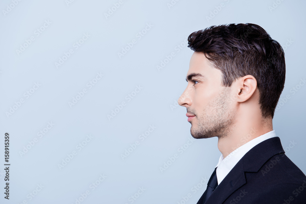 Fototapeta Side profile photo of a young handsome brunete realtor with bristle in a formal wear, standing on the pure blue background next to copyspace