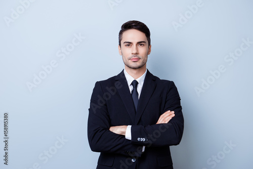 Valokuva  Successful young handsome brunete hispanic man lawyer in a suit on pure background with crossed hands