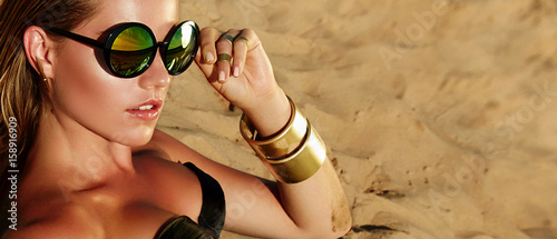 Beautiful young tanned healthy girl in bikini lies on the beach. Bright sun, summer, heat, rest. Accessories - sunglasses, gold bracelets. Beach, sand, rest, travel. Beautiful tanned skin.