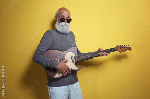 Poster Magasin de musique Senior man with guitar on yellow wall background