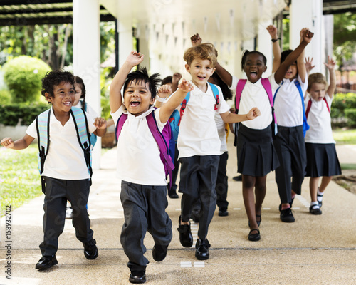 Fotografie, Obraz  Group of diverse kindergarten students running cheerful after school