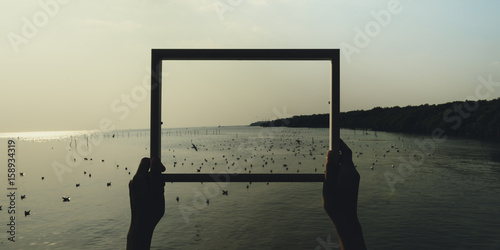 Fotomural Hands Holding Photo Frame Outdoors Ideas